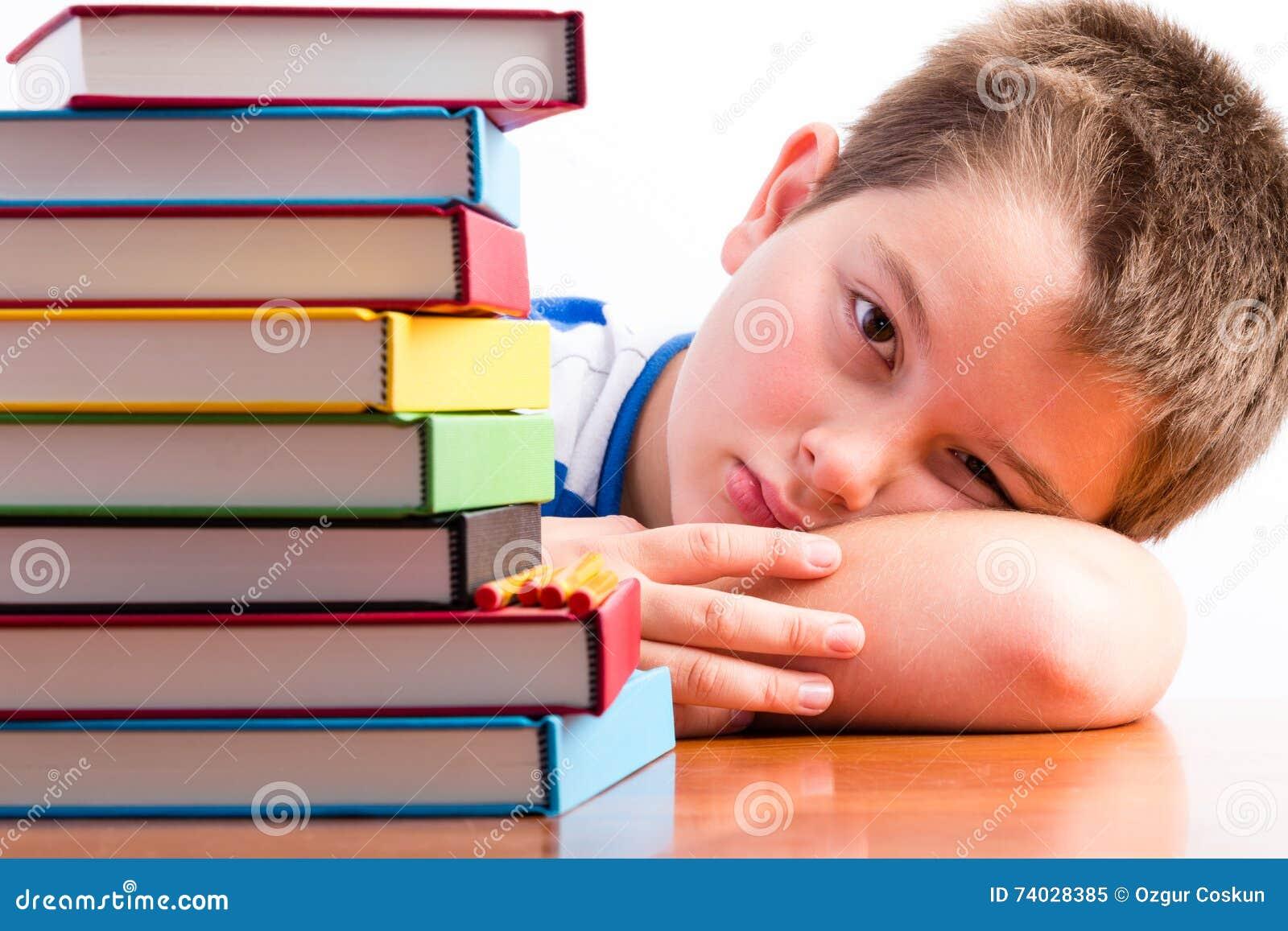 Подавленный молодой школьник наблюдая его учебники