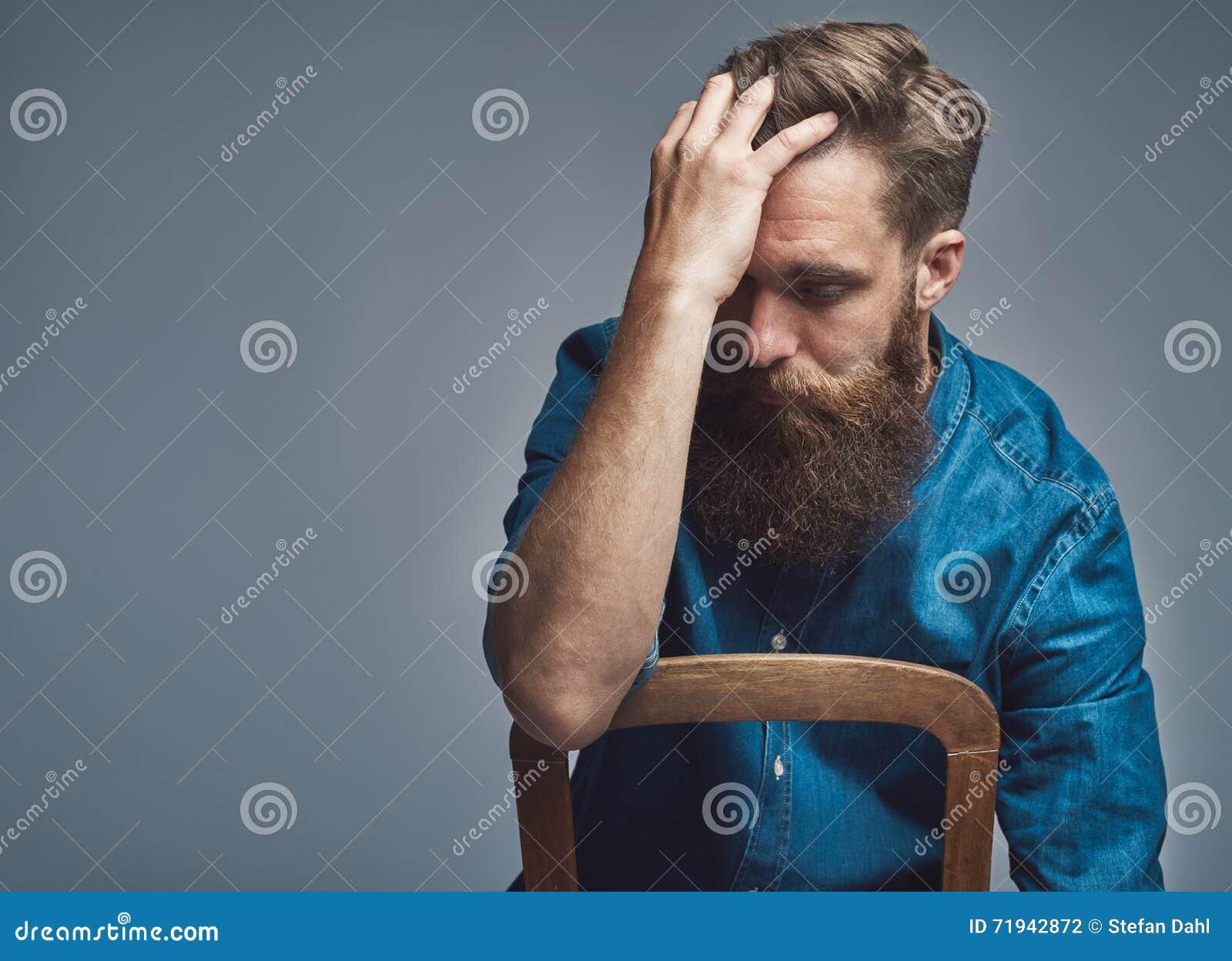 Подавленный человек с рукой на лбе над серым цветом