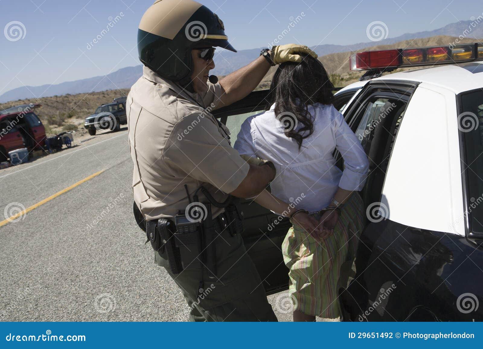 Полисмен арестовывая женского запойного водителя