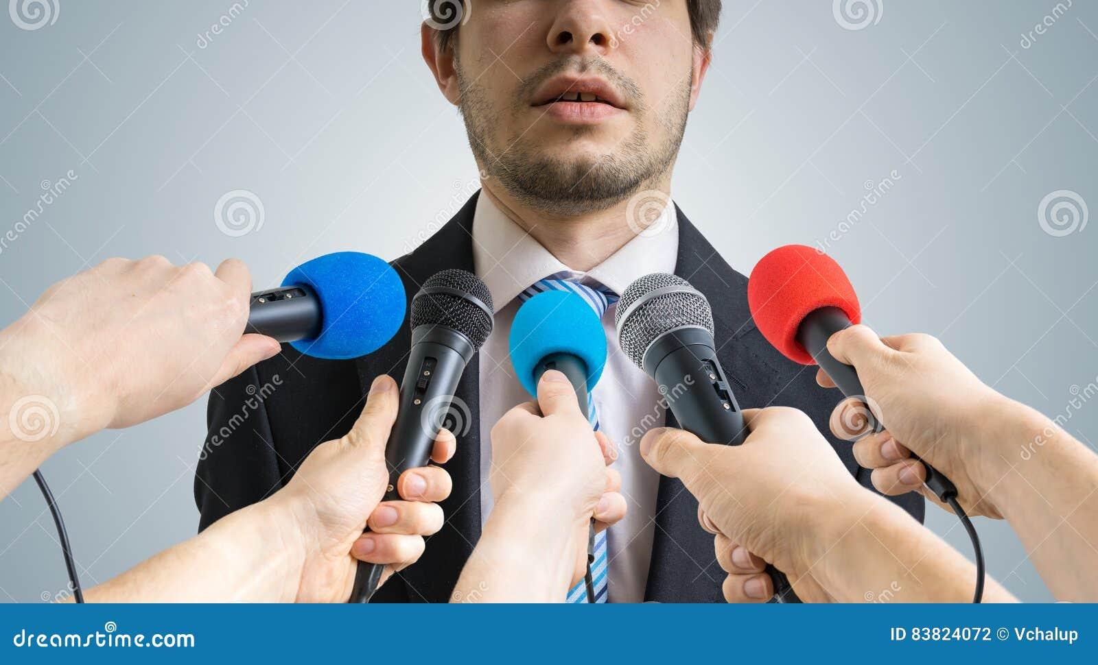 Политик говорит ang давая интервью к репортерам Много микрофонов записывая его