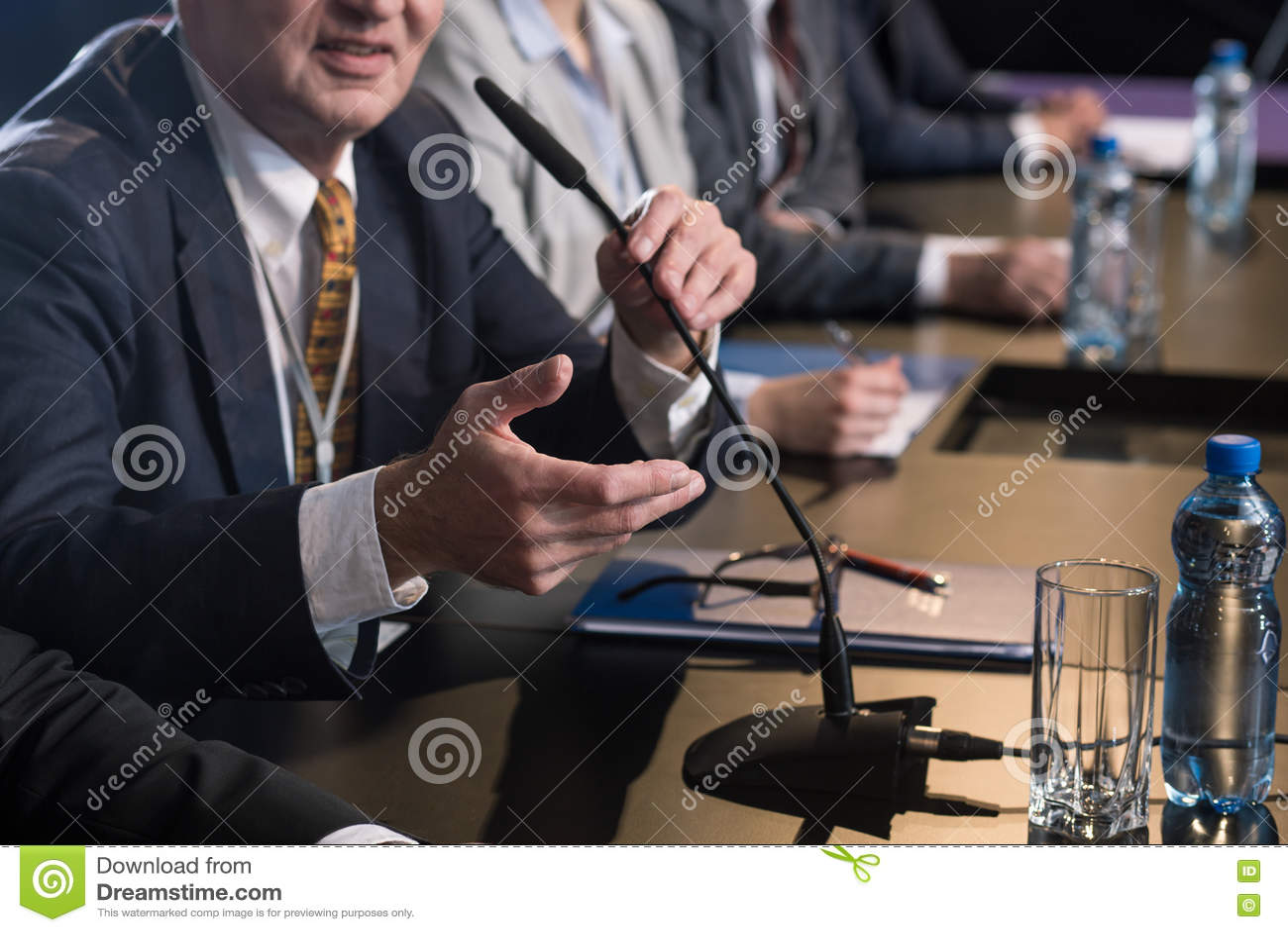 Политик говоря к микрофону