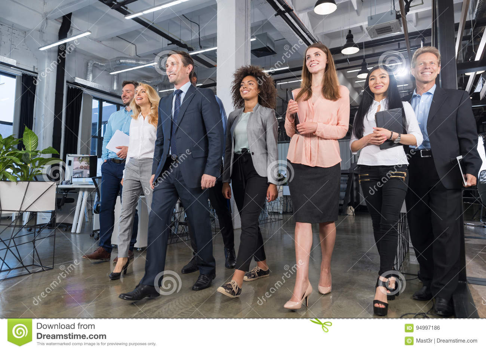 Полнометражные бизнесмены команды идя в современный офис, уверенно бизнесменов и коммерсанток в костюмах разнообразных с