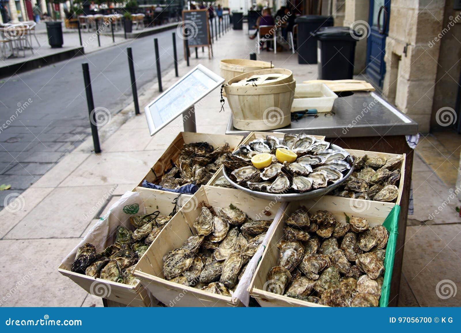 Поднос раскрытых свежих устриц на льде с лимоном и коробками неоткрытых устриц на кафе улицы в Бордо, Аквитании fran