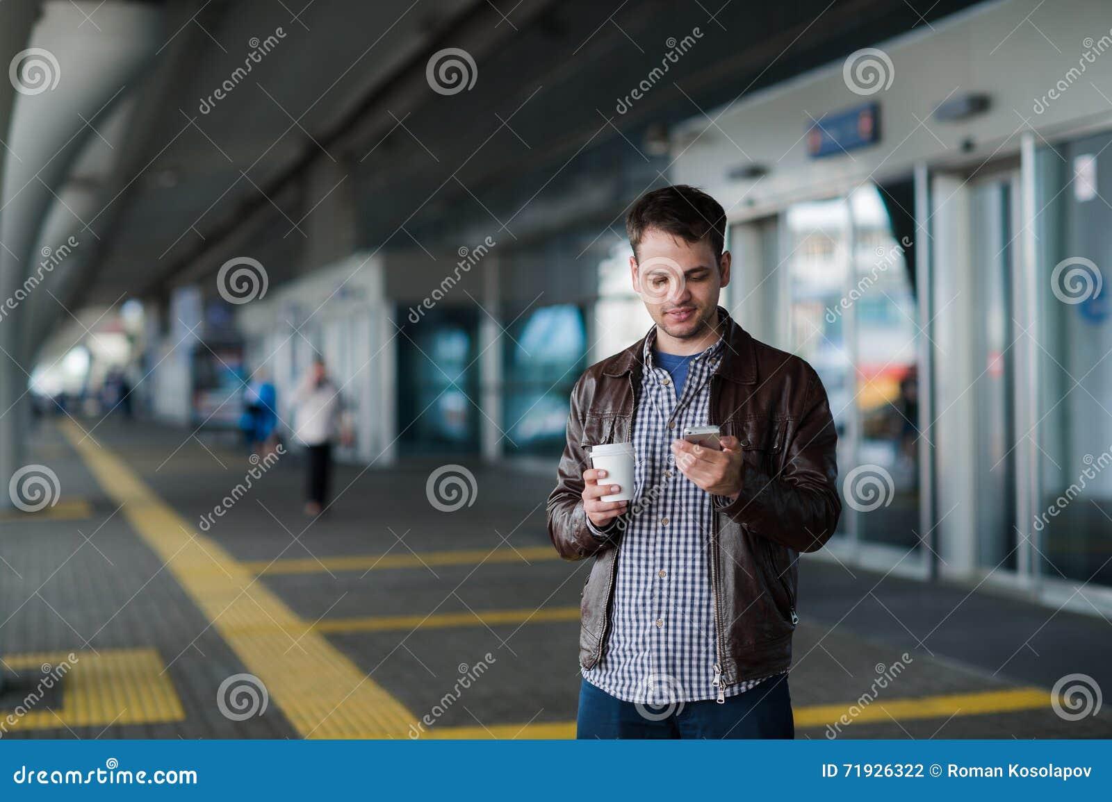 Полный портрет тела мужского путешественника идя с мобильным телефоном и кофе
