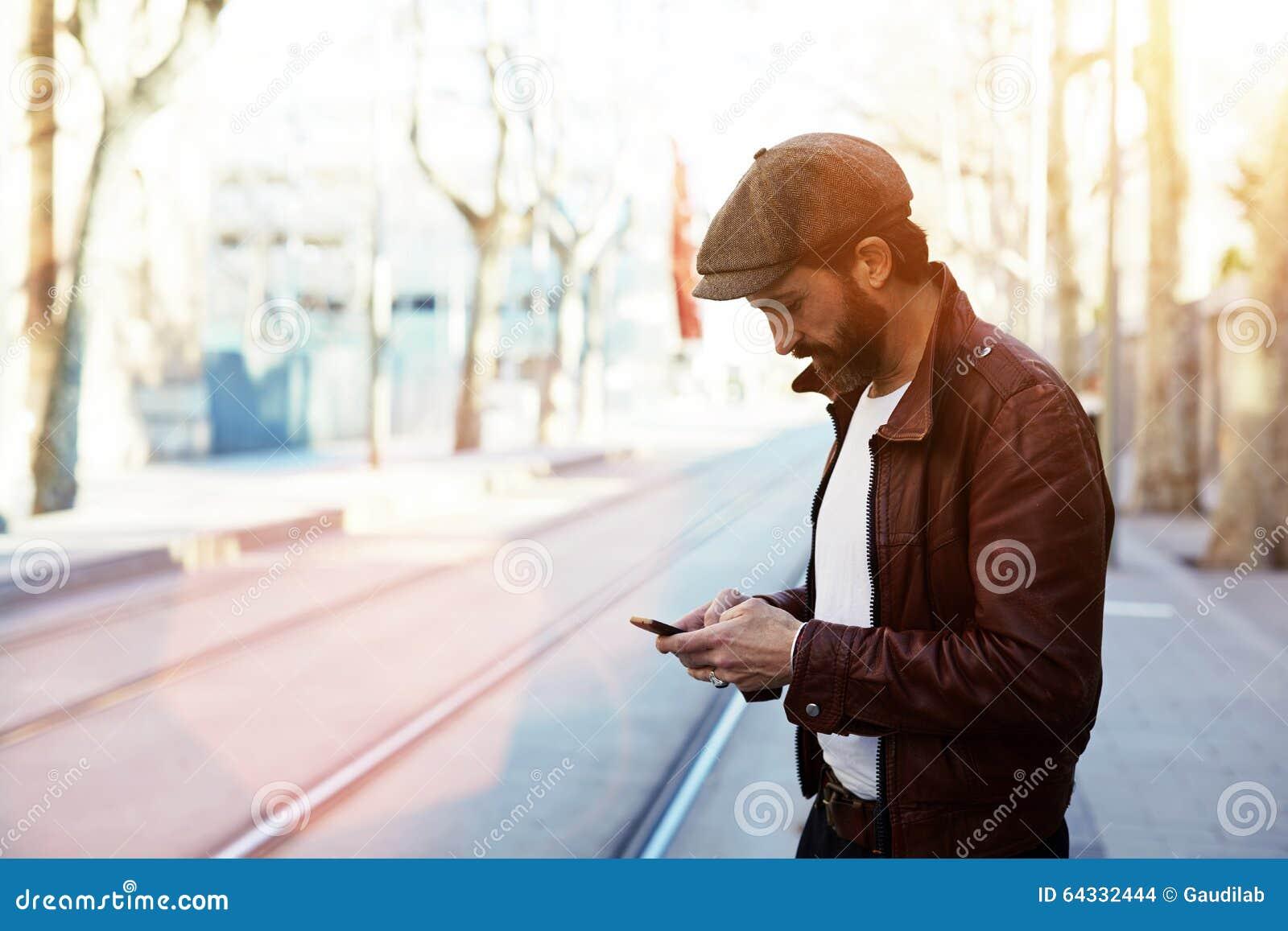 Половинный портрет длины бородатого человека битника одел в стильных одеждах беседуя на телефоне клетки пока стоящ в улице
