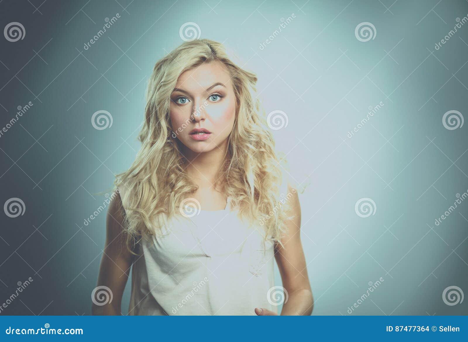 Положение молодой женщины, изолированное на серой предпосылке