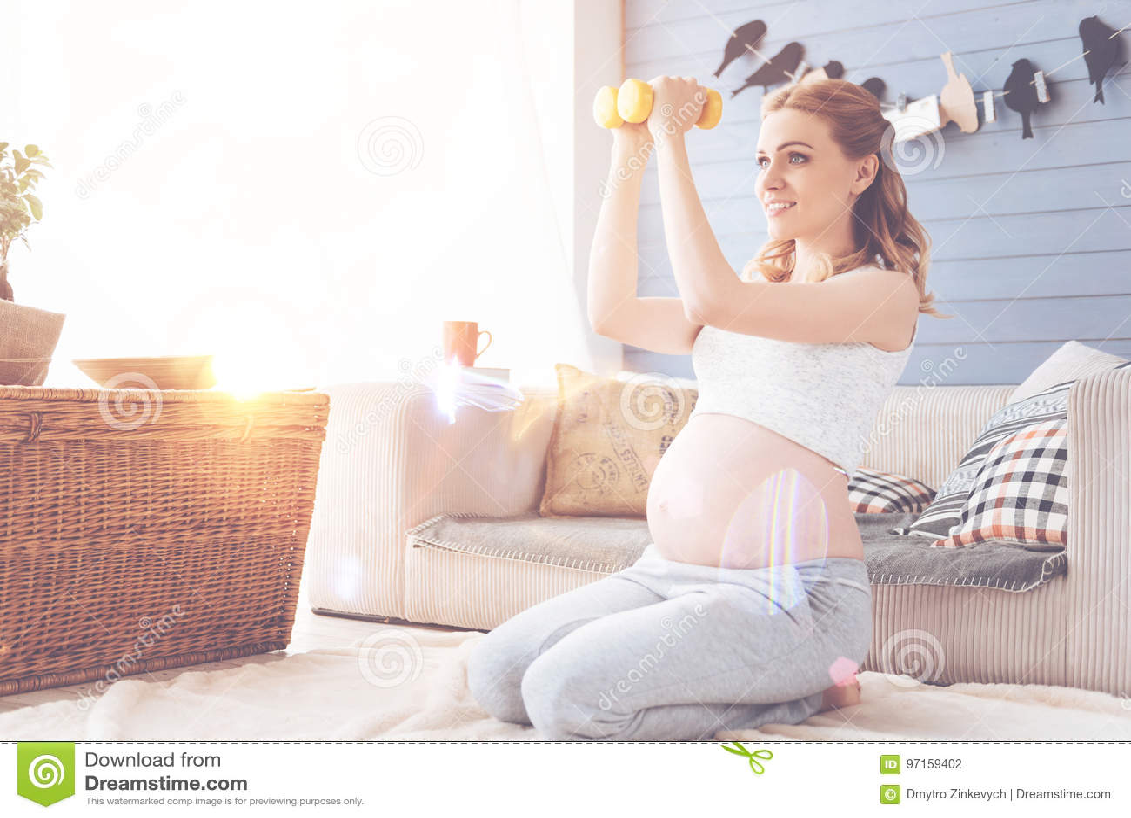 Положительная красивая беременная женщина делая тренировки спорта