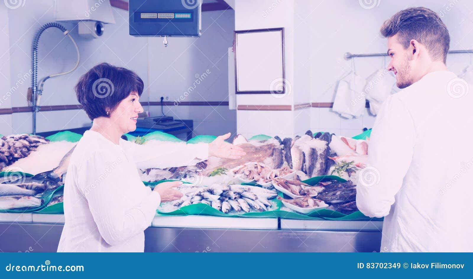 Положительные клиенты выбирая морепродукты в магазине