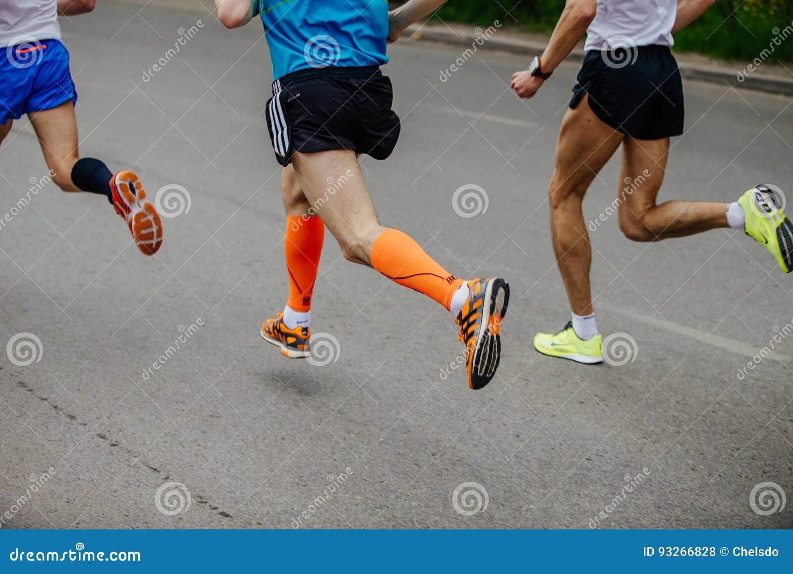 Подоприте бегуна 3 людей бежать на улице города