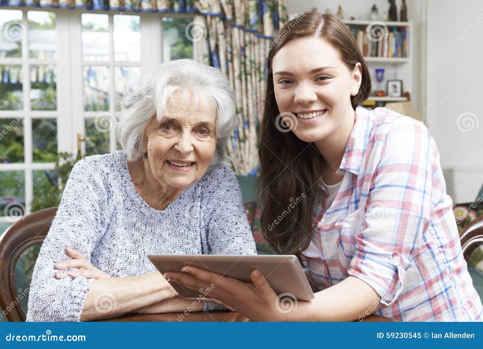 Подростковой бабушке внучки показывающ как использовать плату цифров