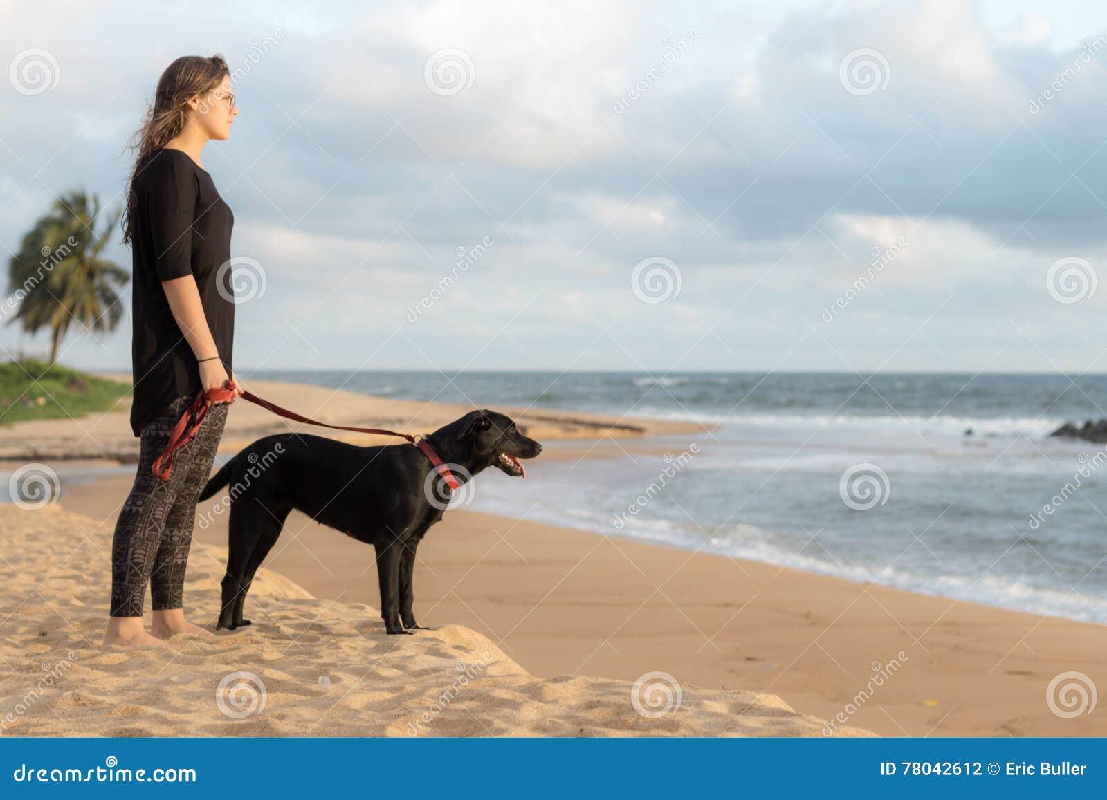 Подросток и ее собака на пляже