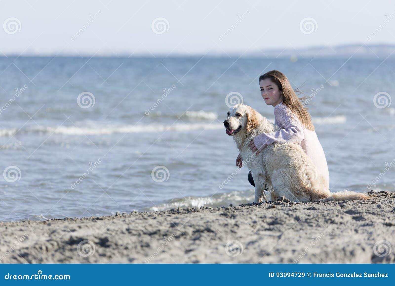 Подросток с ее собакой на пляже