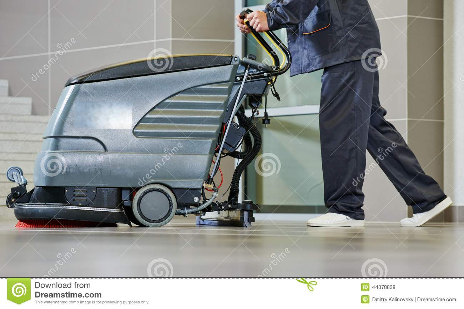 Пол чистки работника с машиной