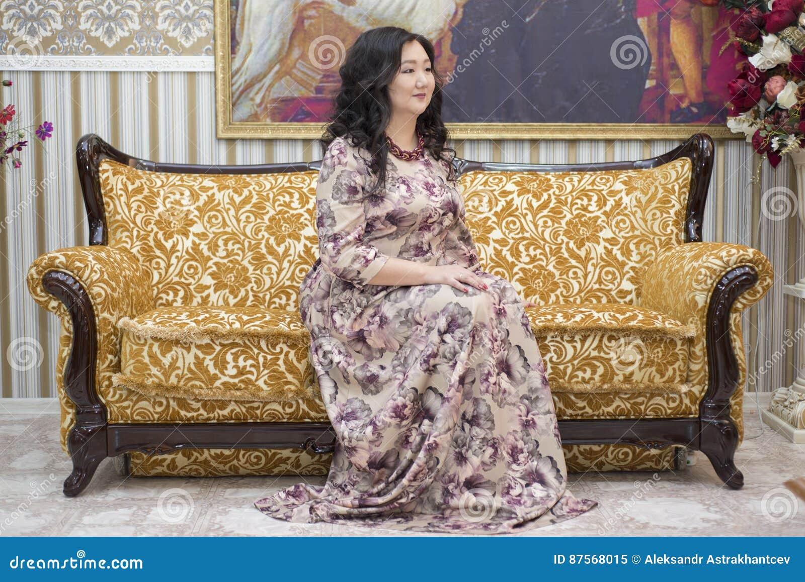 Польностью азиатская женщина сидя на софе в живущей комнате