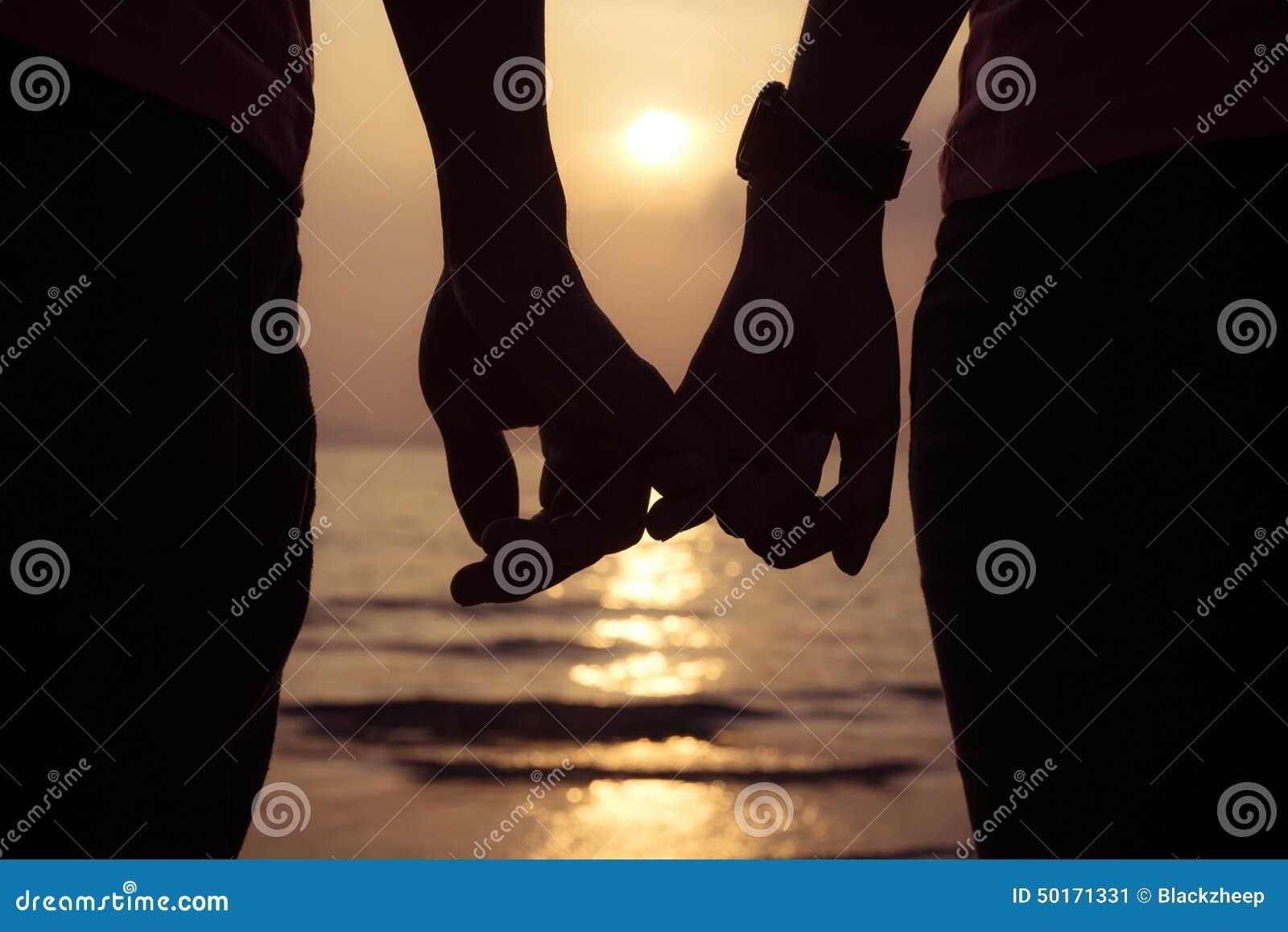 полюбите пар держа пальцы рук на заходе солнца на пляже