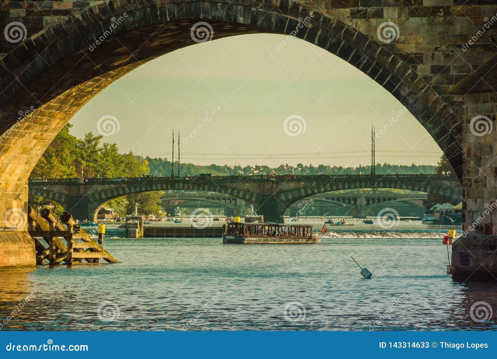 Прага, чехия - 17-ое сентября 2019: Туристы идя Карлов мост trought, взгляд от уровня реки Влтавы