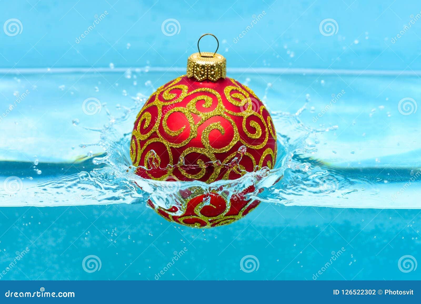 Праздники и концепция каникул Праздничное украшение для рождественской елки, красный шарик с оформлением яркого блеска упало в во