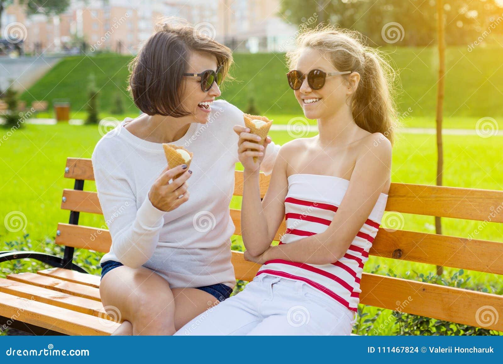 Праздник с семьей Счастливая молодая мать и милый подросток дочери в городе паркуют еду мороженого, говорить и смеяться над