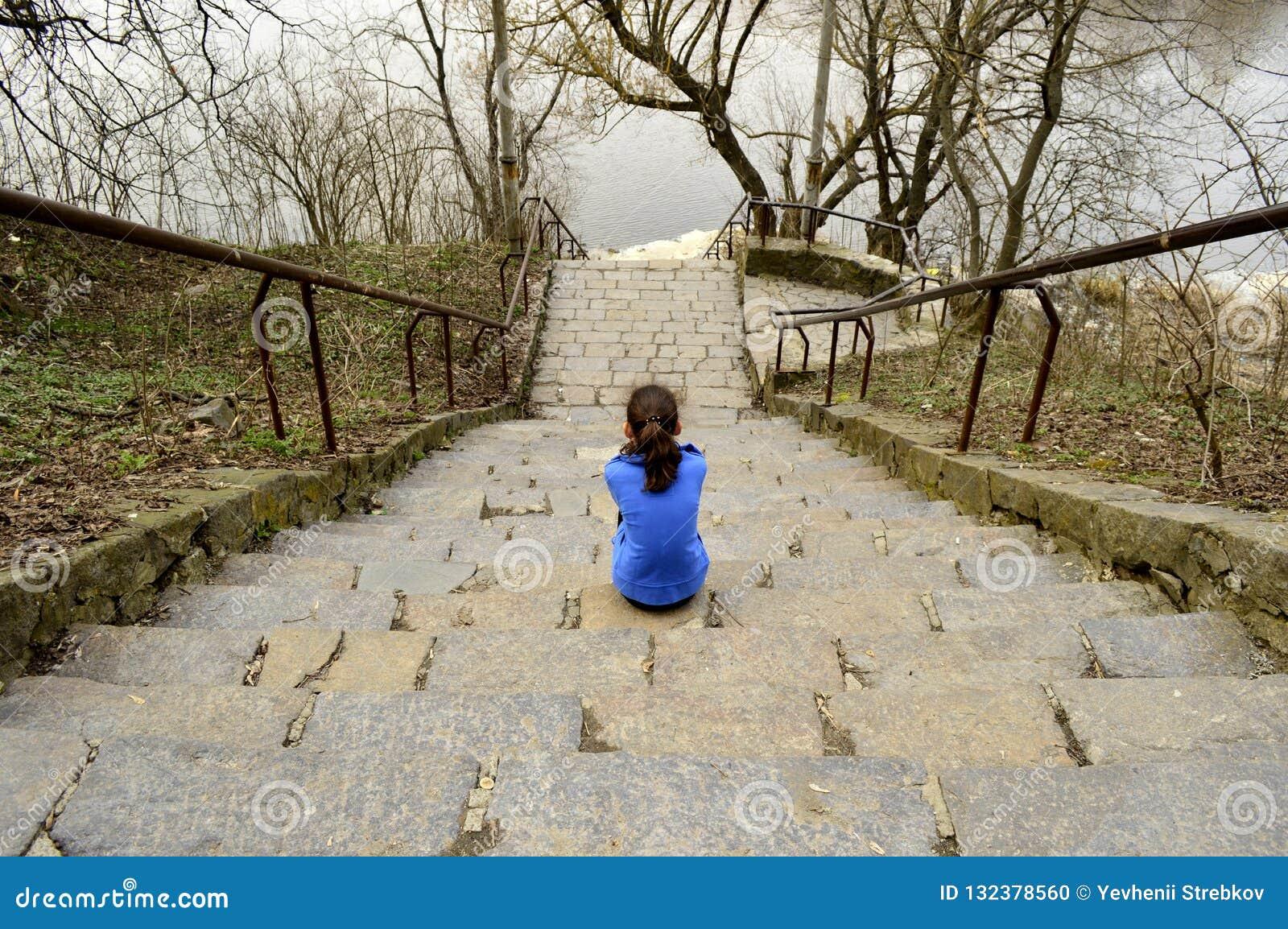 Предназначенная для подростков девушка сидя на шагах
