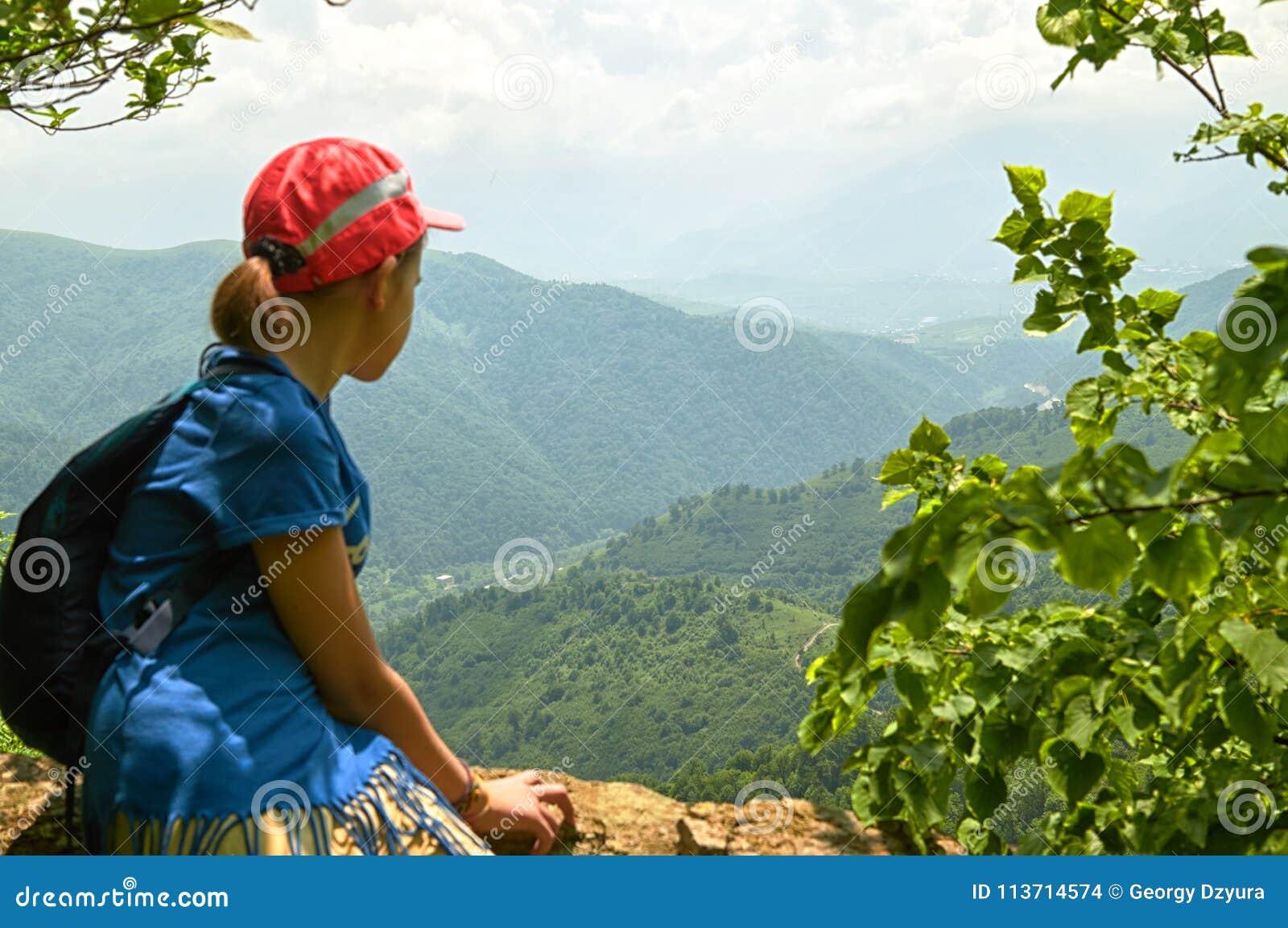 Предназначенная для подростков девушка hiker сидя на высокой скале в армянских горах в солнечном летнем дне