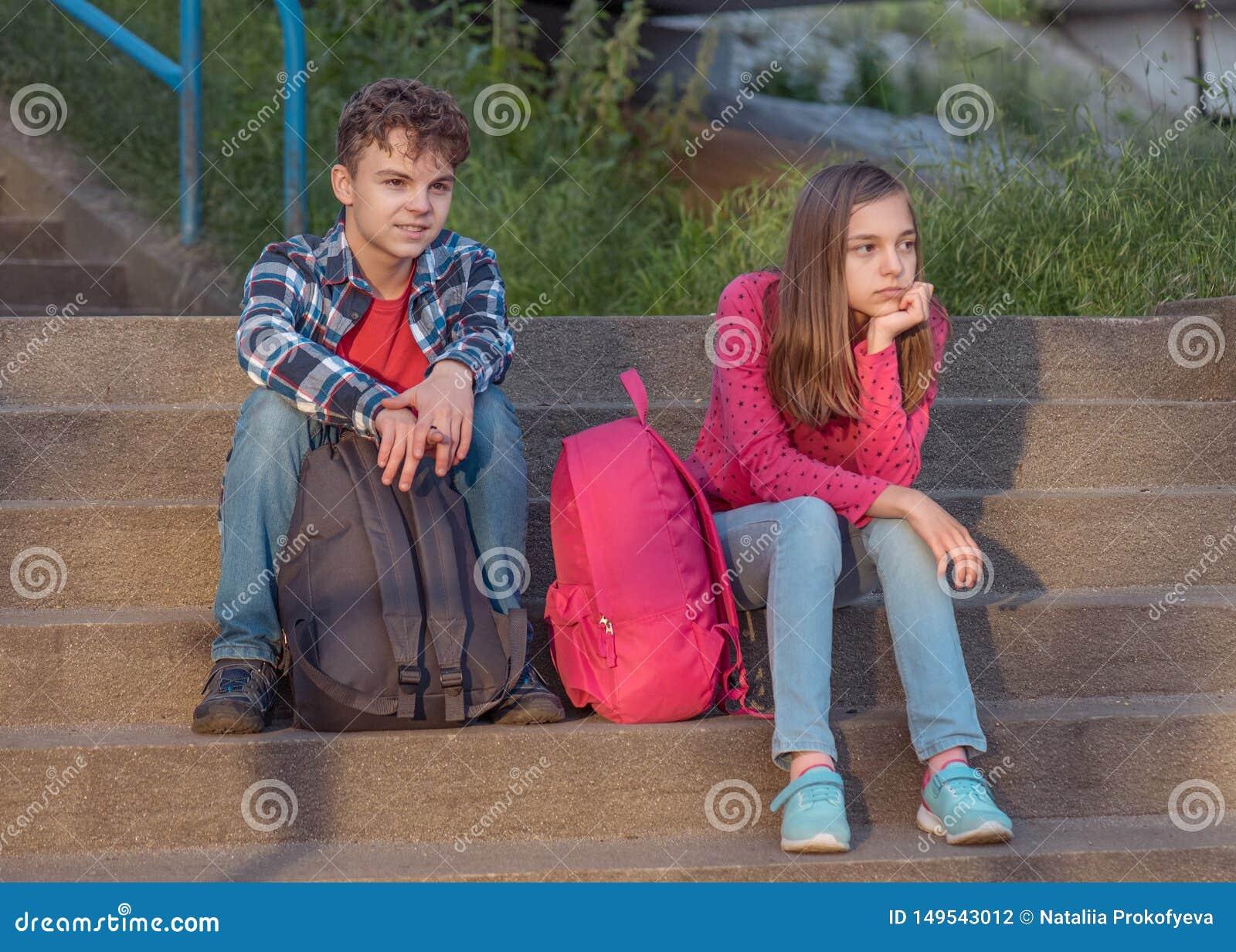Предназначенный для подростков мальчик и девушка сидя на лестницах