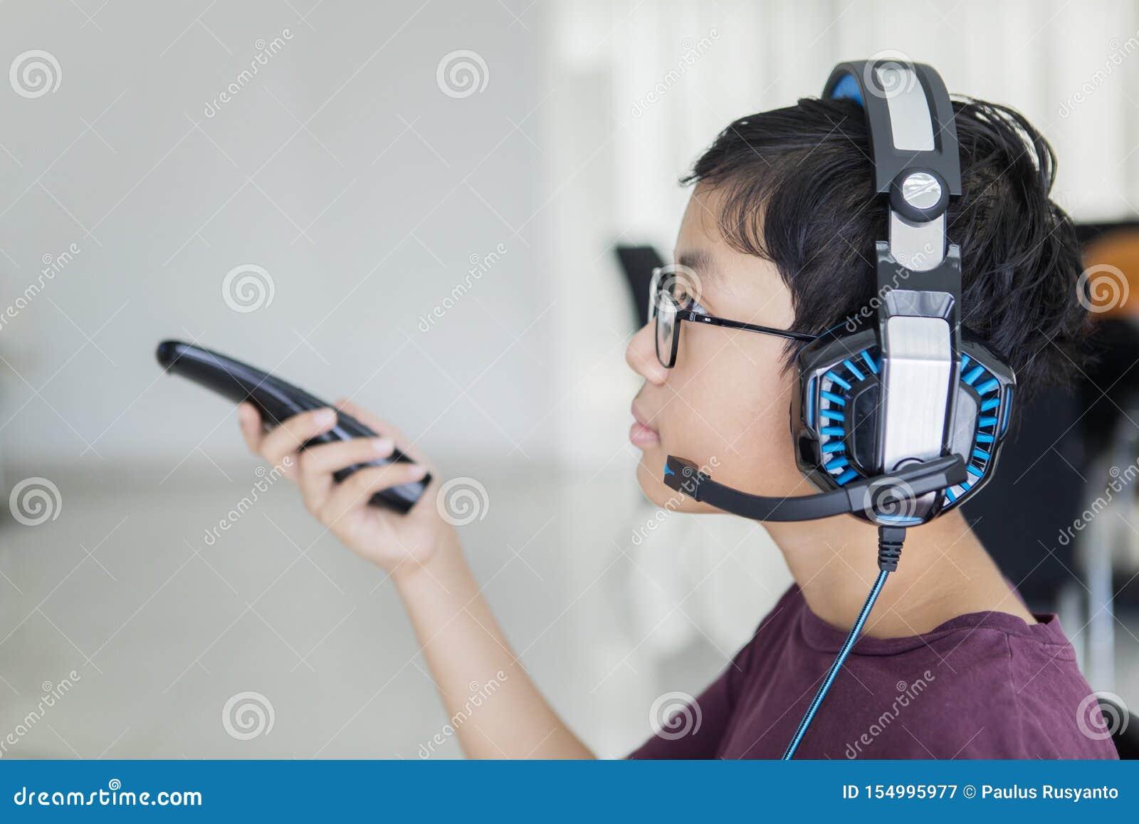 Предназначенный для подростков мальчик смотря ТВ с наушниками