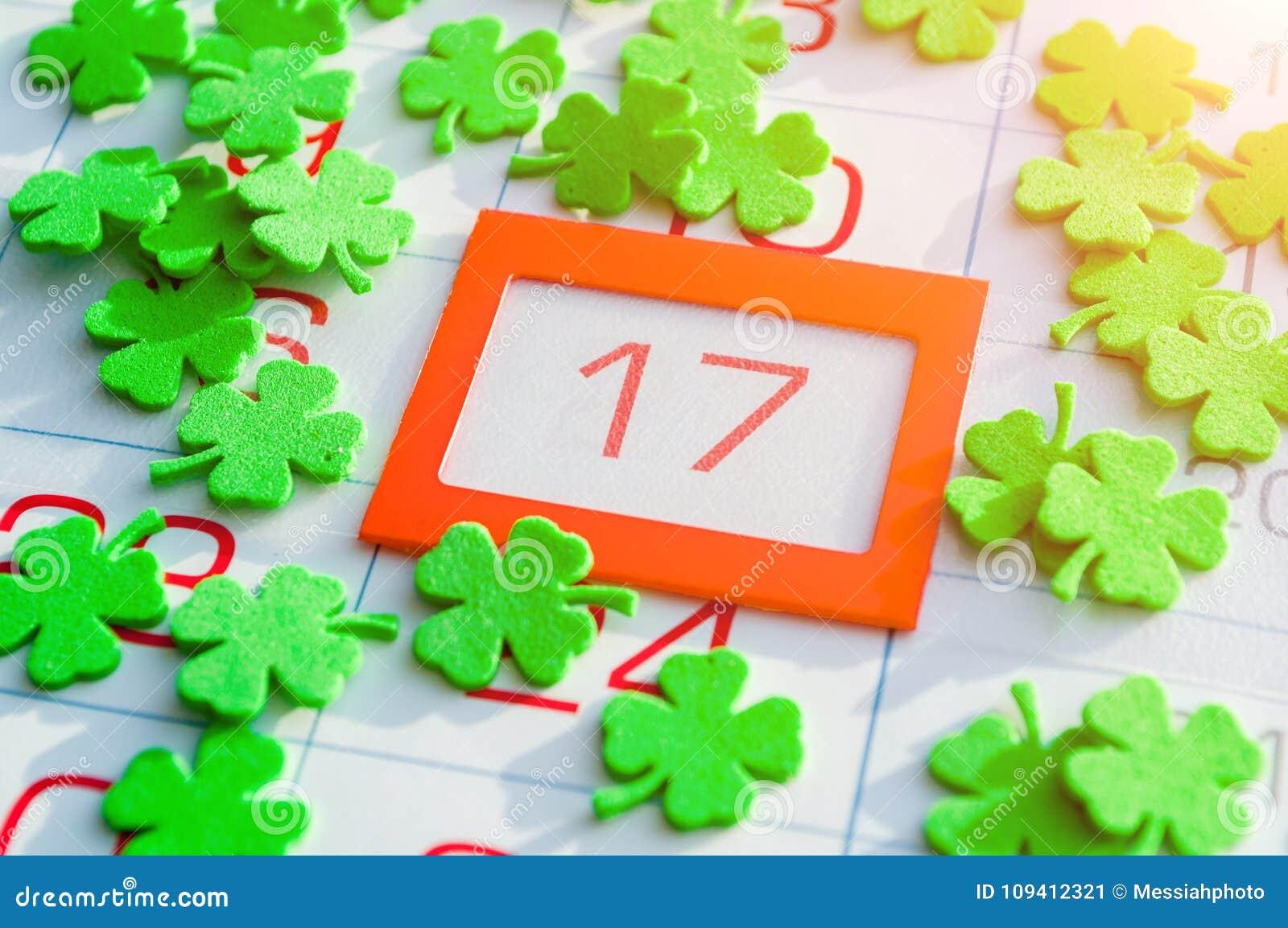Предпосылка дня ` s St. Patrick праздничная Зеленые quatrefoils покрывая календарь с ярким апельсином обрамили 17-ое марта