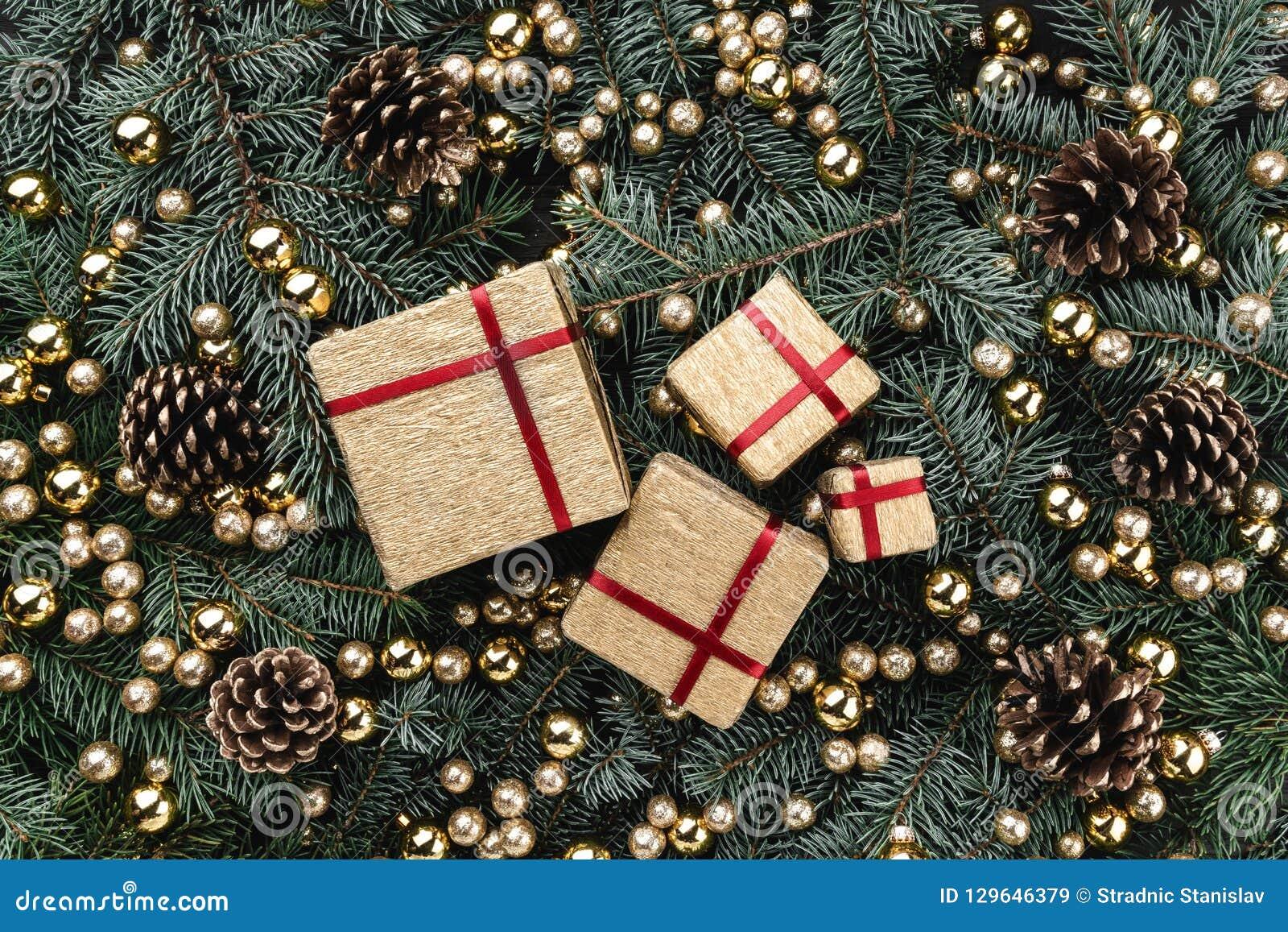 Предпосылка зимы ветвей ели Украшенный с безделушками, конусами и подарками золота небо klaus santa заморозка рождества карточки