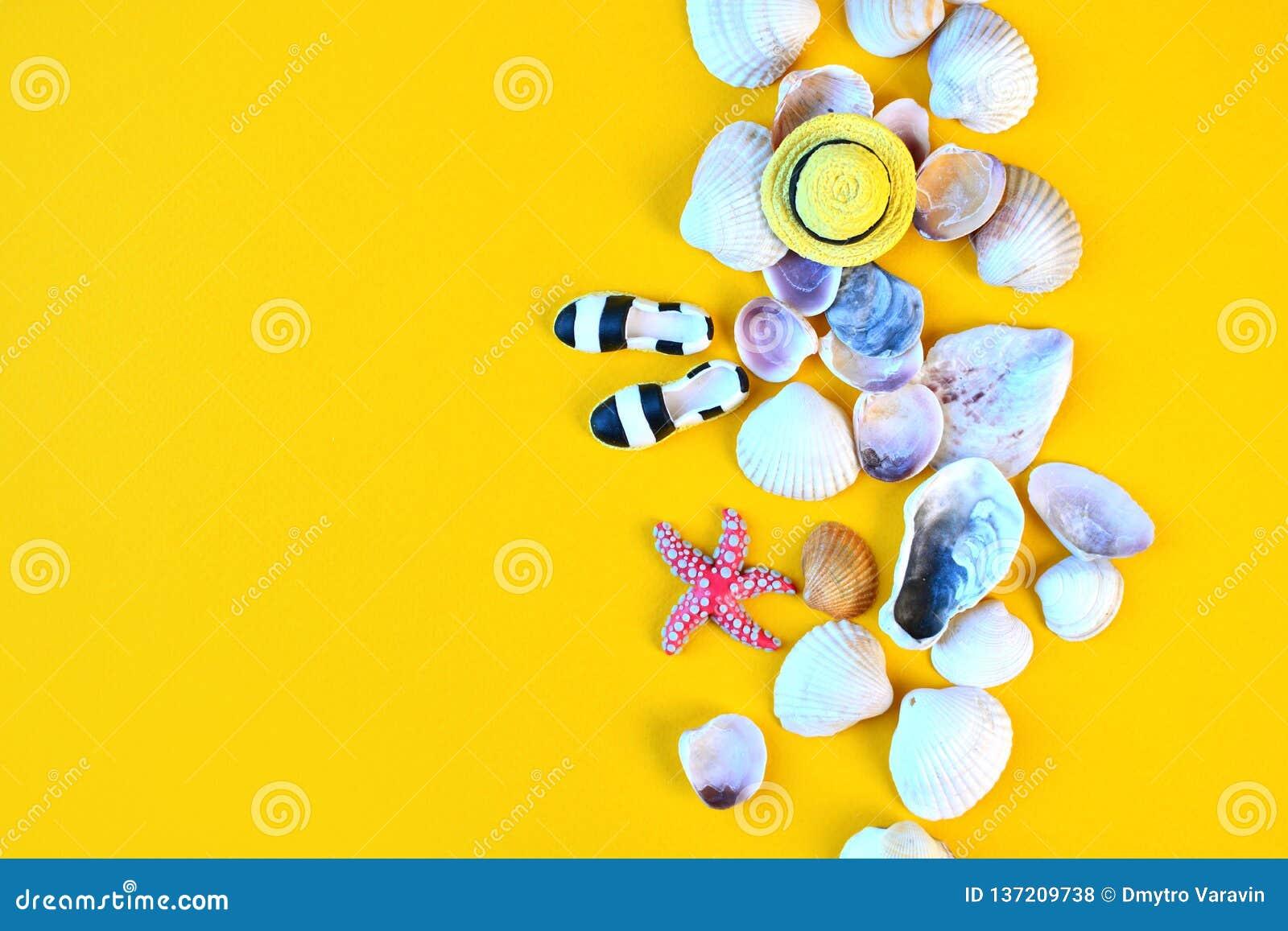 Предпосылка лета Плоские положенные аксессуары пляжа путешественника на желтой предпосылке с seashells, миниатюрной шляпой и mocc