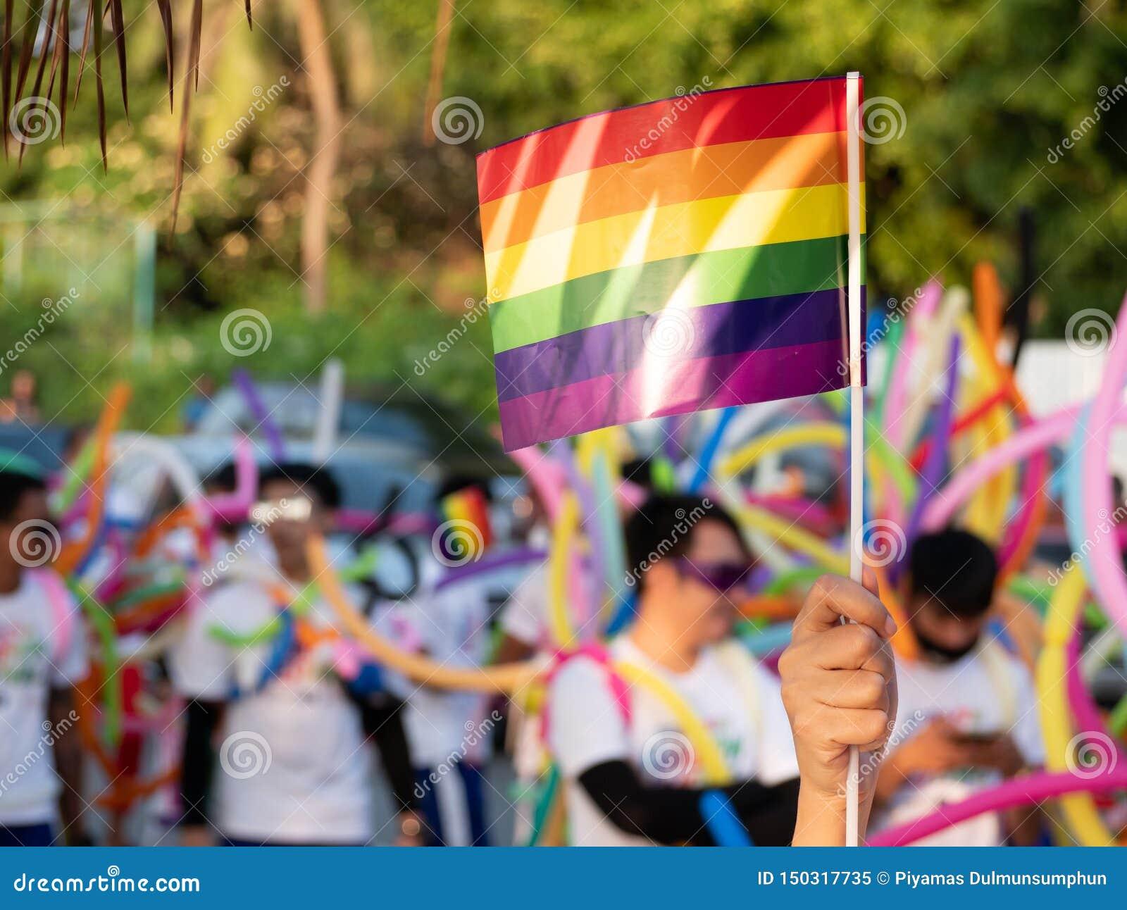 Предпосылка месяца гордости LGBT зритель развевает флаг радуги гея на фестивале парада гей-парада LGBT в Таиланде