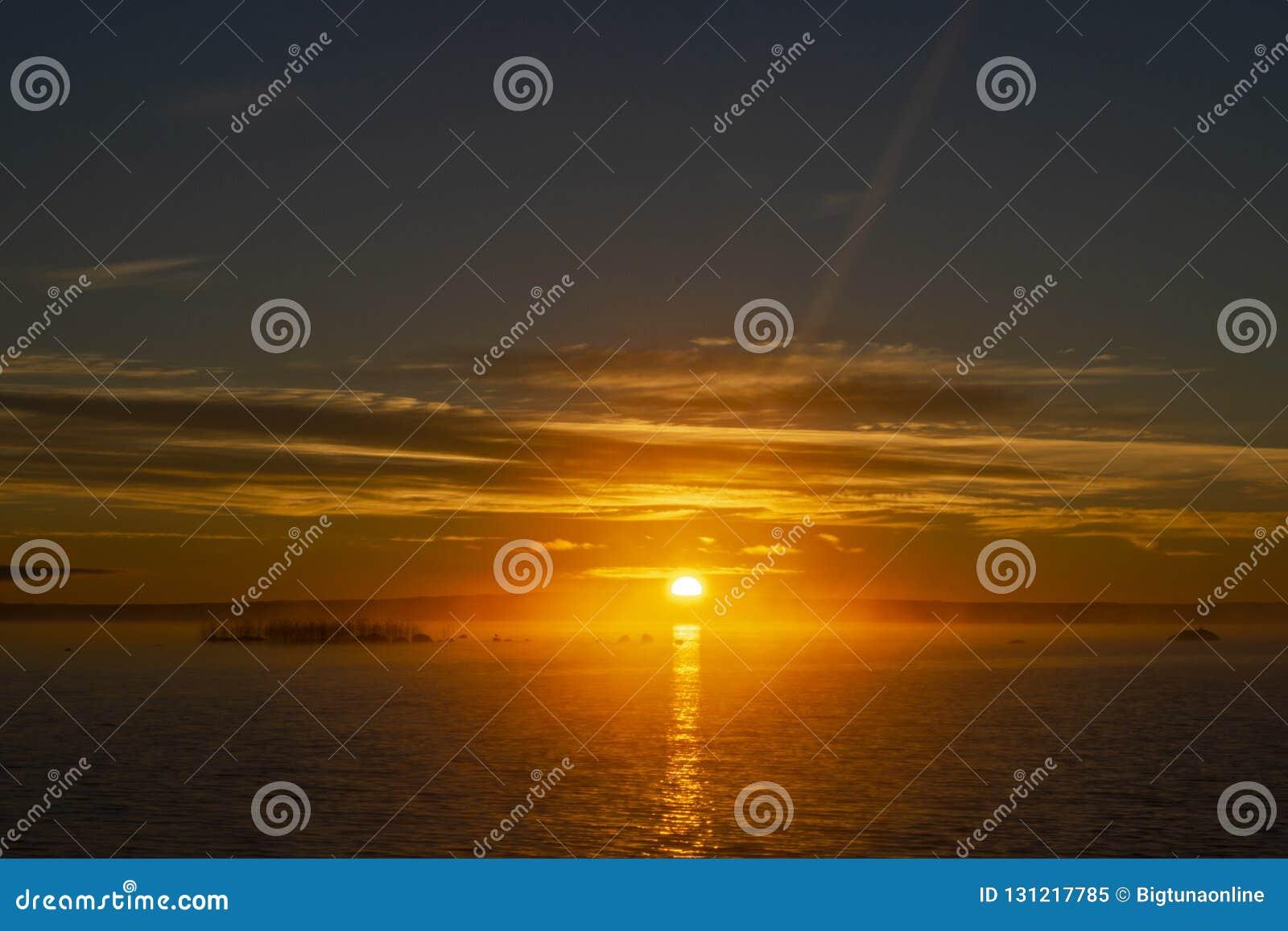 Предпосылка неба захода солнца Драматическое небо захода солнца золота с небом вечера заволакивает над морем  Земля неба