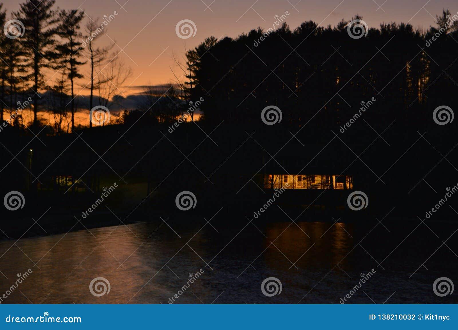Предпосылка пейзажа сценарного ландшафта вечера захода солнца силуэта дома вида на озеро мирная