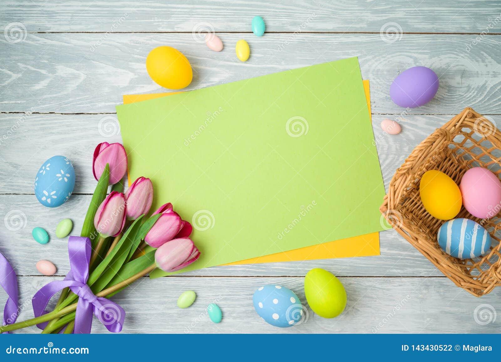 Предпосылка праздника пасхи с примечанием бумаги, пасхальные яйца в корзине и цветки тюльпана на деревянном столе
