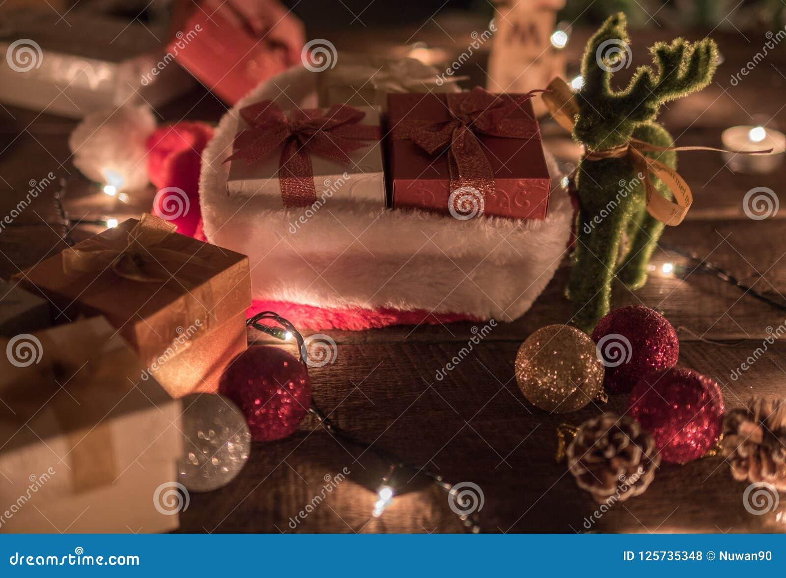 Предпосылка рождества с шариком рождества, подарочными коробками, шляпой Санты, светами северного оленя и рождества на деревянной
