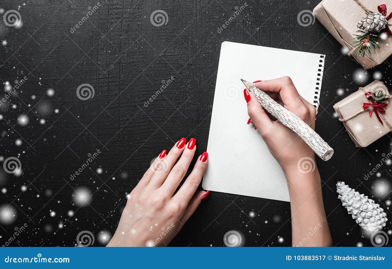 Предпосылка рождественской открытки - руки женщины при красные ногти писать письмо с деревянным карандашем