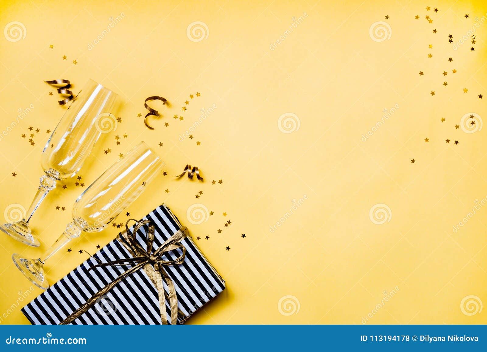 Предпосылка торжества - взгляд сверху 2 chrystal стекел шампанского, подарочная коробка обернутая в черно-белой striped бумаге, л