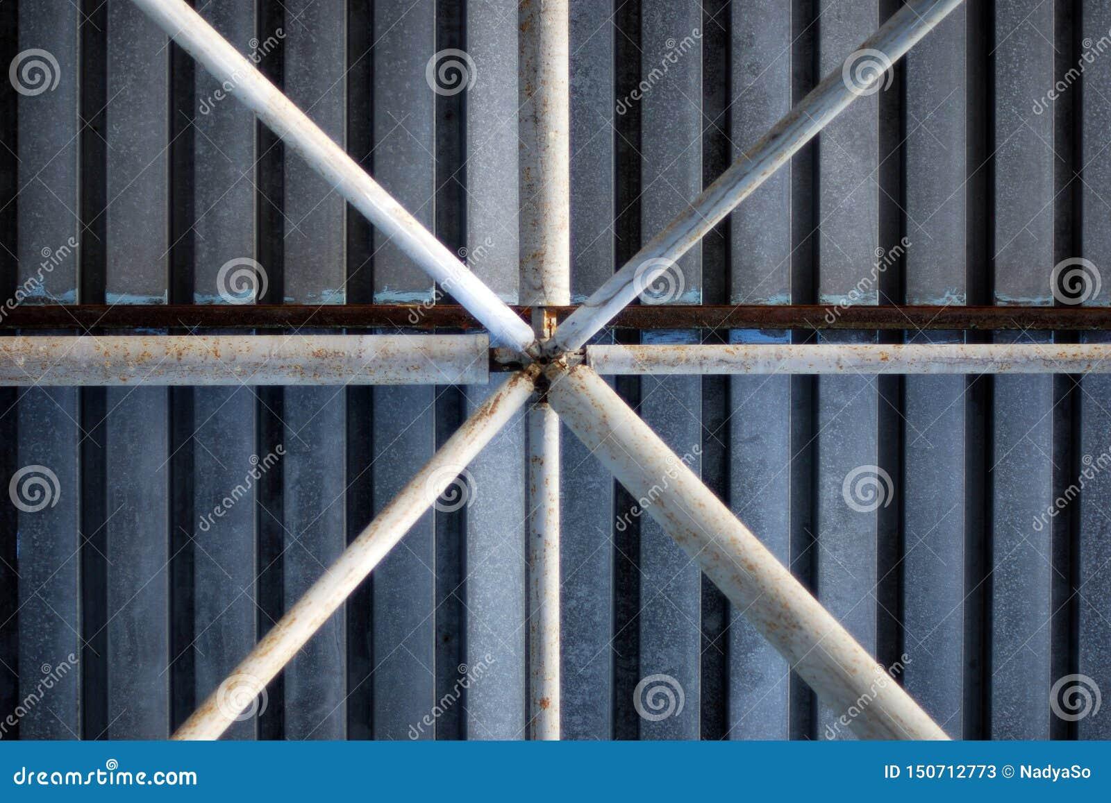 Предпосылка труб металла под гальванизированной крышей гаража автопарка