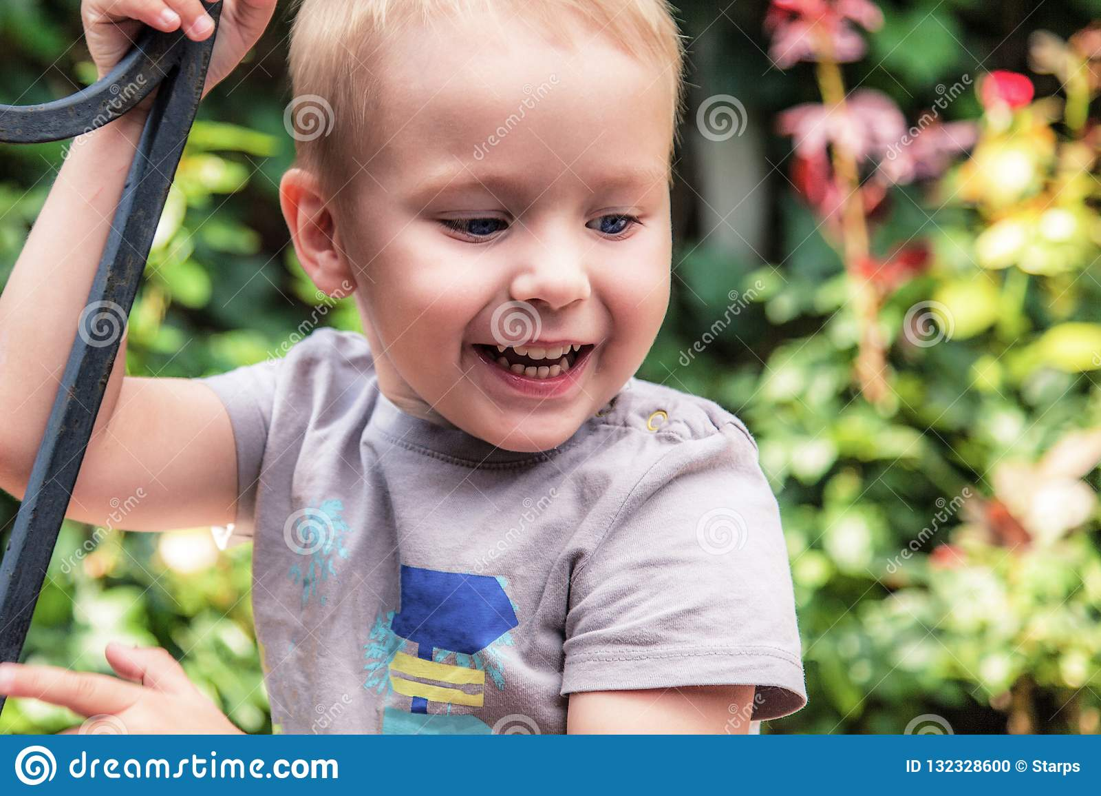 Предпосылка цветков на открытом воздухе ot милого ребенка усмехаясь зеленая