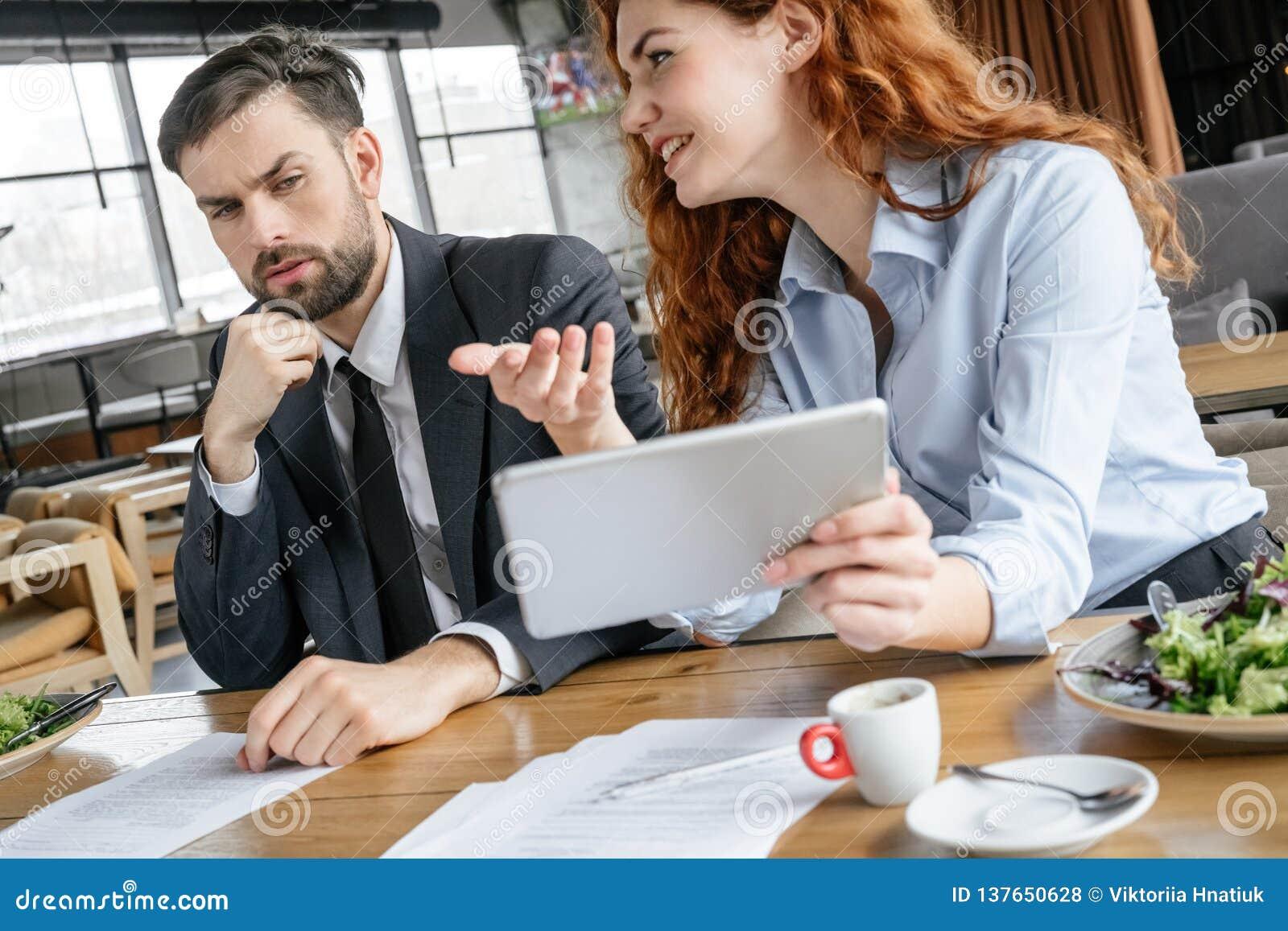 Предприниматели имея бизнес-ланч на идее показа женщины ресторана сидя на цифровом планшете пока смотреть человека