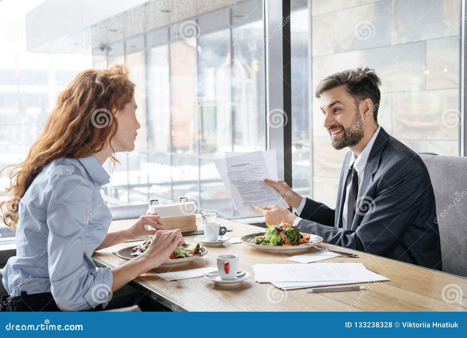 Предприниматели имея бизнес-ланч на ресторане сидя около окна есть салат обсуждая проект жизнерадостный