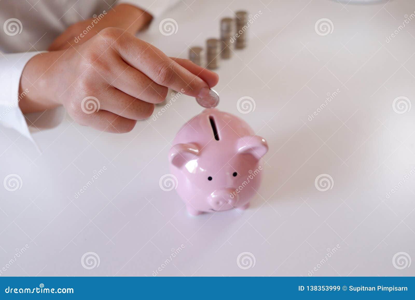 Предприниматель вводя монетки в копилку со стогом монеток над столом