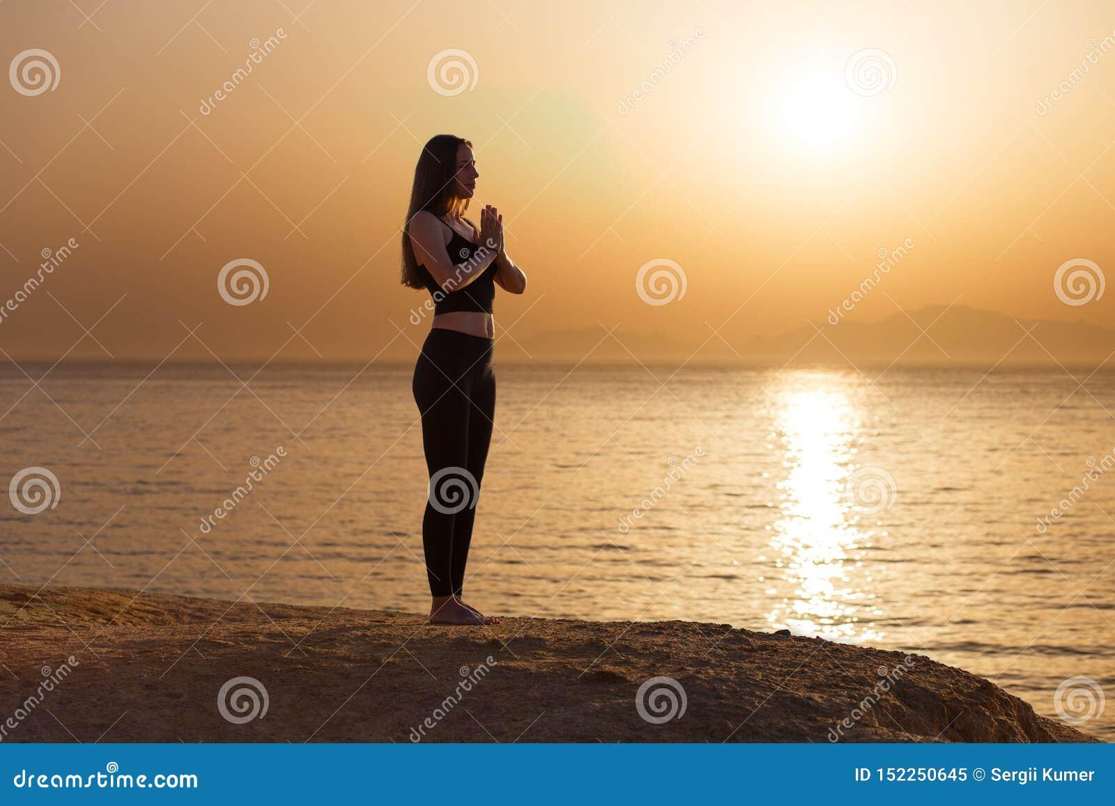 Представление asana йоги молодой женщины практикуя в утро на море