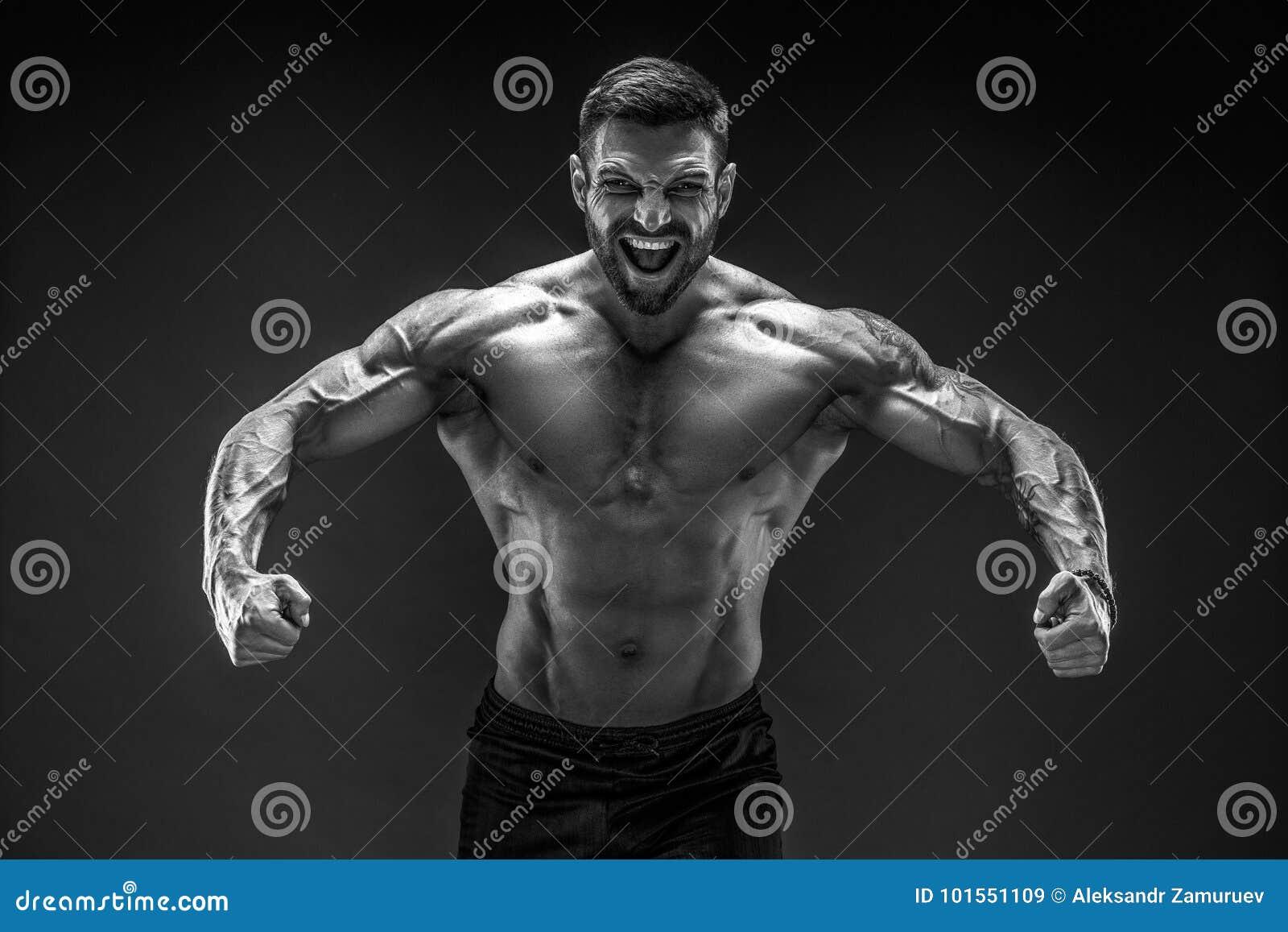 представлять культуриста Человек muscled фитнесом на темной предпосылке рык