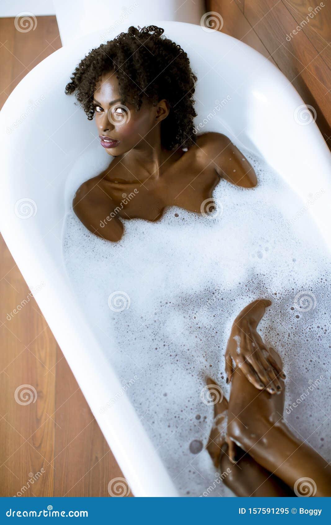 Молодая женщина купается в ванне с пеной