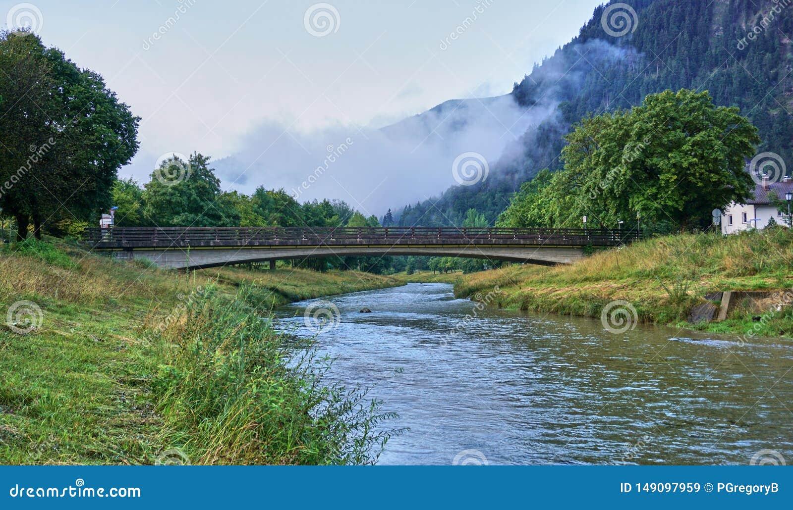 Прекрасный пешеходный мост над рекой Ammer в Баварии
