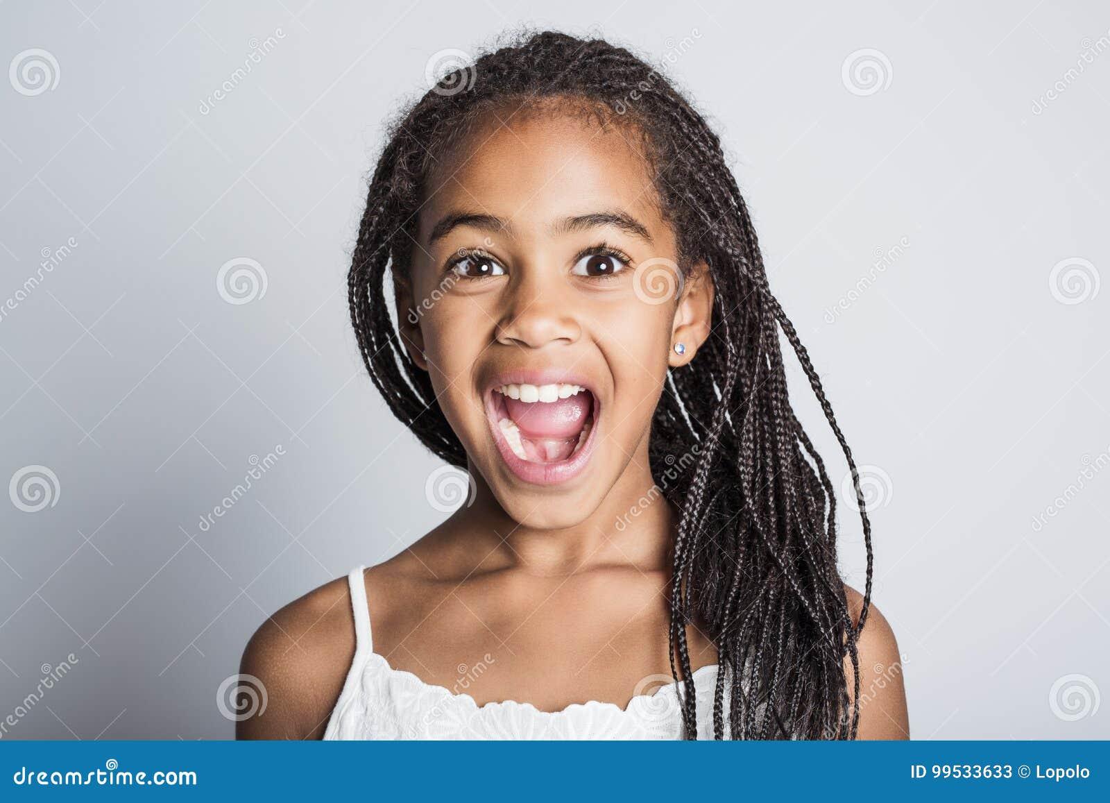 Прелестная африканская маленькая девочка на предпосылке серого цвета студии