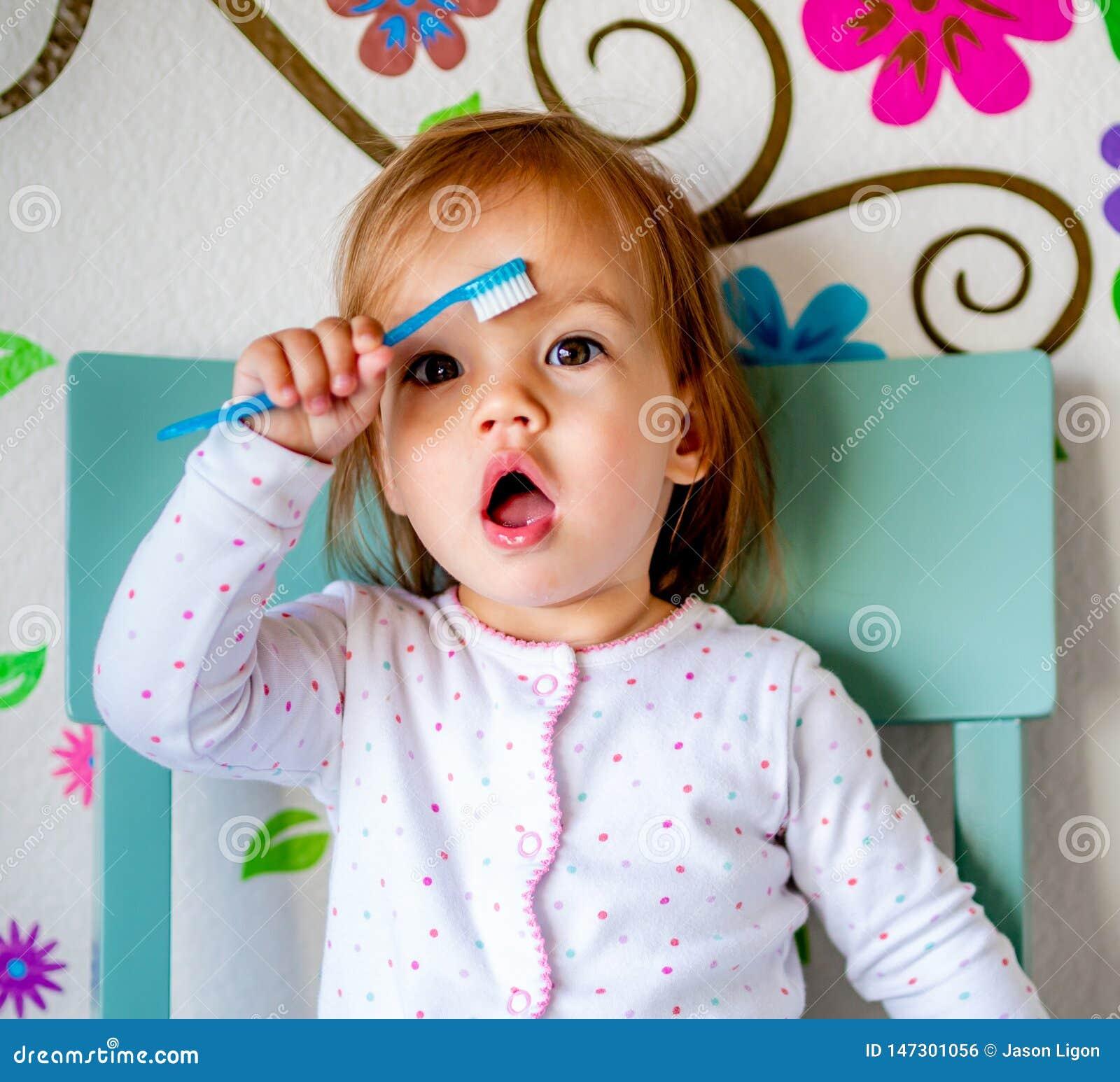 Прелестная девушка малыша чистит ее зубы щеткой в пижамах E