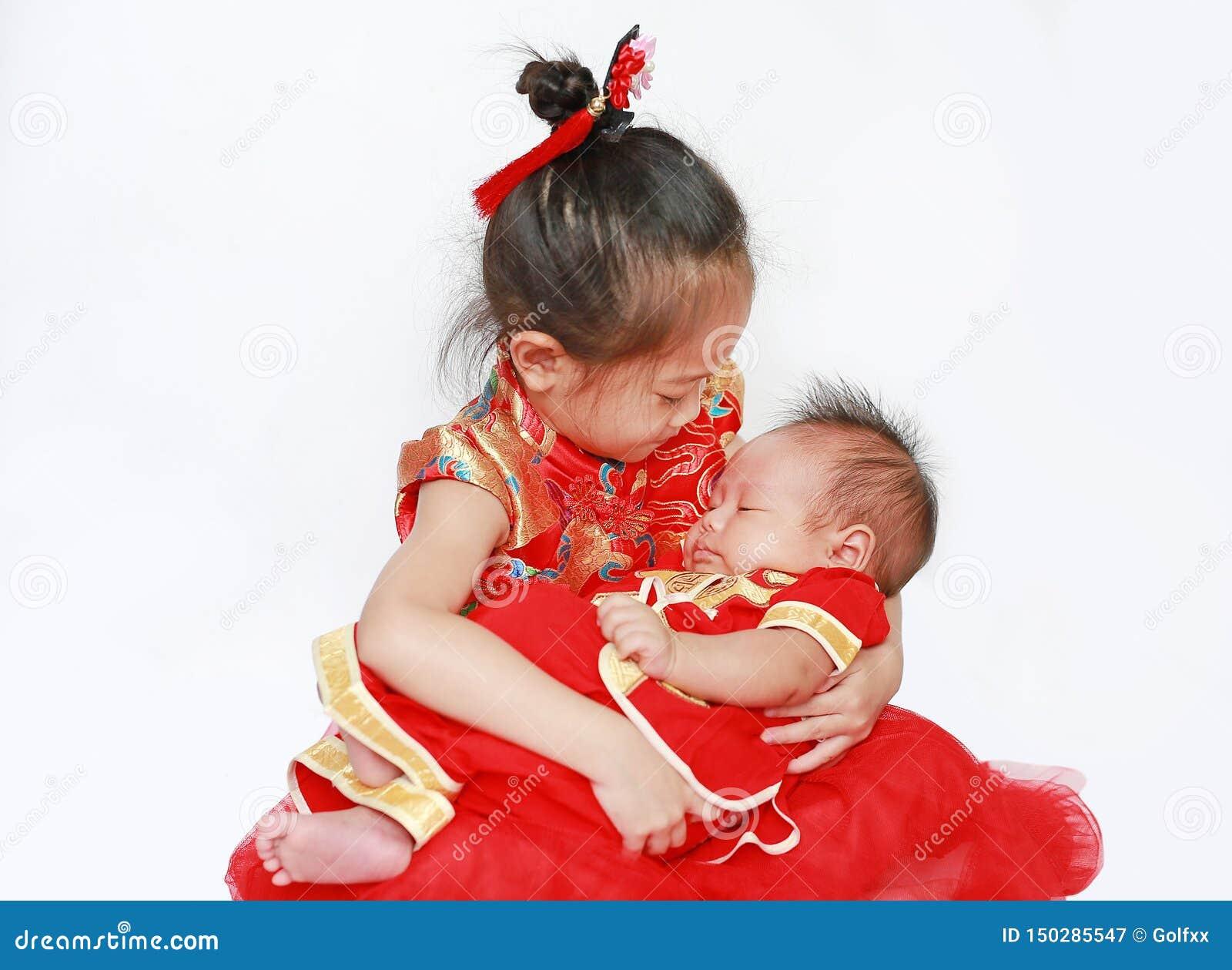 Прелестная маленькая азиатская девушка и младенческий ребенок в cheongsam изолированном на белой предпосылке во время Нового Года