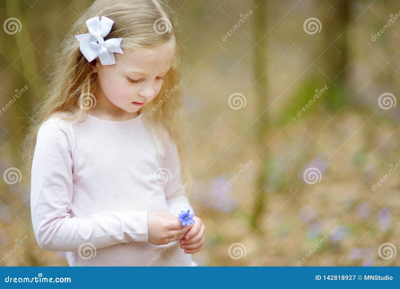 Прелестная маленькая девочка выбирая первые цветки весны в древесинах на красивый солнечный весенний день
