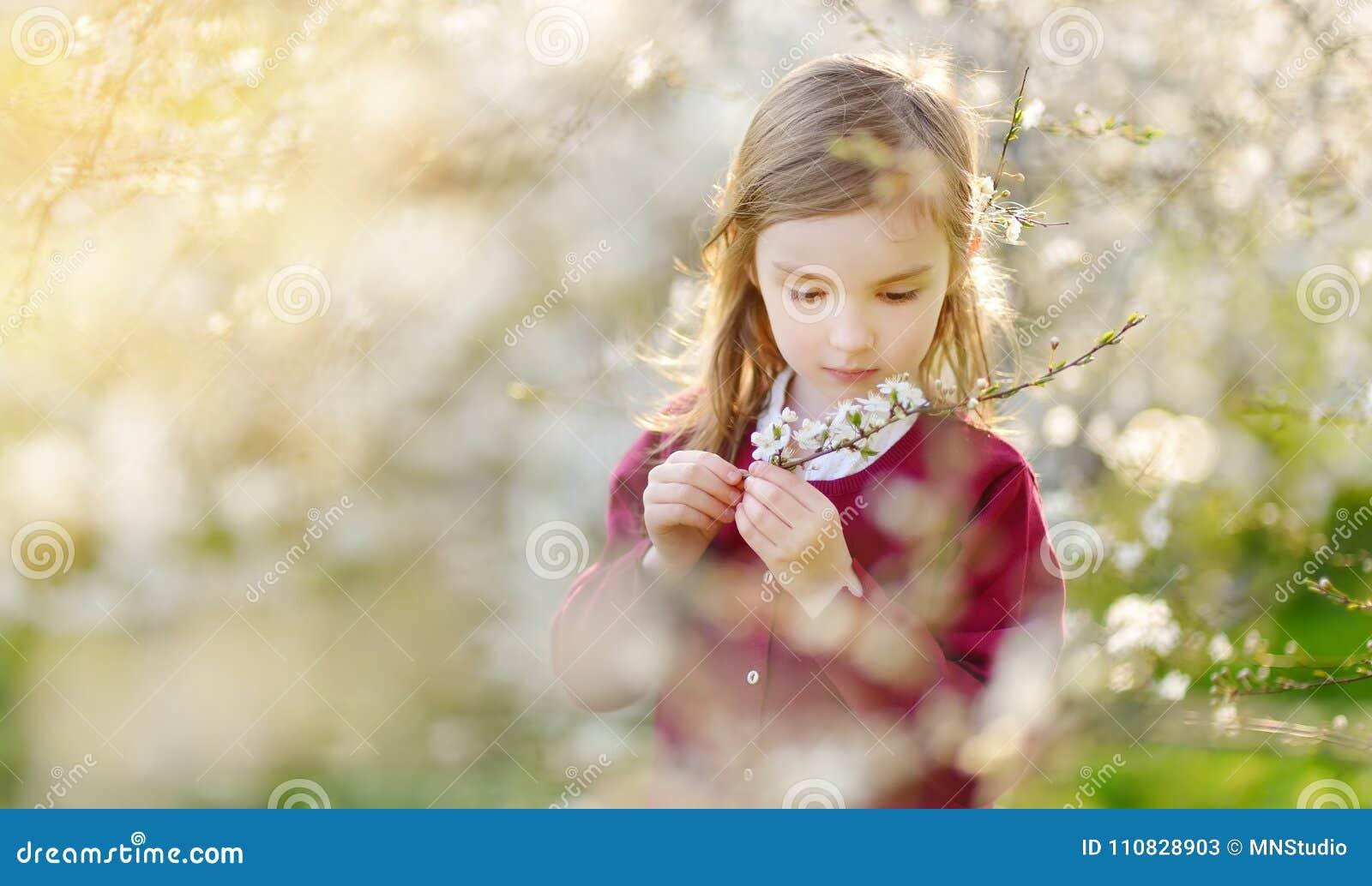 Прелестная маленькая девочка в зацветая саде вишневого дерева на красивый весенний день